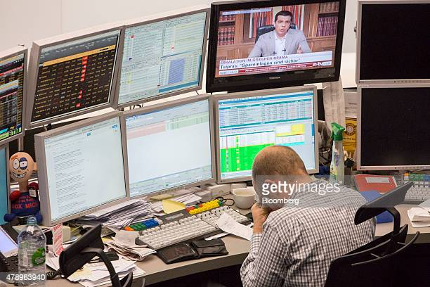 A financial trader reacts at his desk as a television screen displays Alexis Tsipras Greece's prime minister during a news report at the Frankfurt...