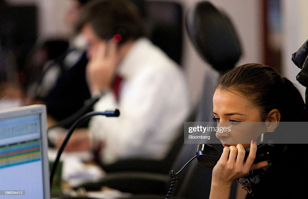 A financial trader speaks on the telephone as she works from her desk at Aurel BGC's brokerage in Paris, France, on Monday, Nov. 12, 2012. European stocks fluctuated between gains and losses as finance ministers prepared to discuss Greek aid after the country's lawmakers approved the 2013 budget. Photographer: Balint Porneczi/Bloomberg via Getty Images