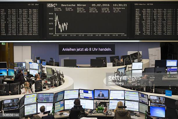 Financial traders monitor data as the DAX Index curve and stock price information is displayed on boards inside Frankfurt Stock Exchange in Frankfurt...