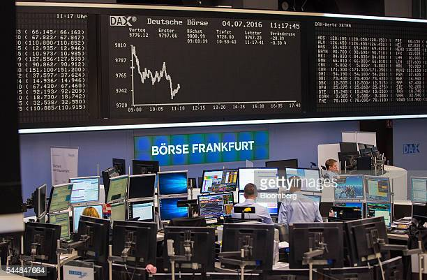 Financial traders monitor data on computer screens as the DAX Index curve sits on an electronic board above inside the Frankfurt Stock Exchange in...