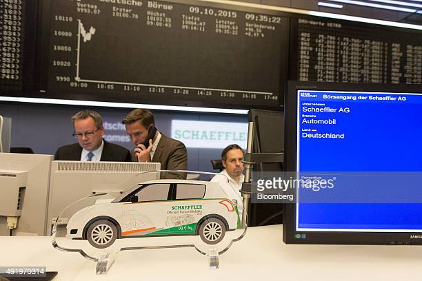 Financial traders monitor data on computer screens as the Schaeffler AG stock information and merchandise sit on display inside the Frankfurt Stock...