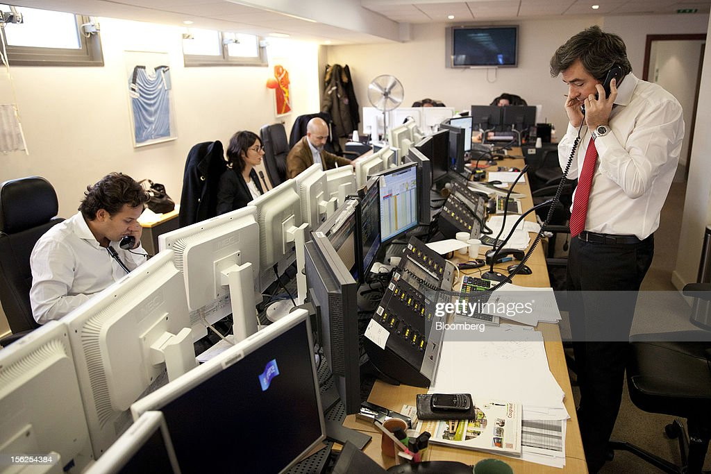 Financial traders speak on telephones as they monitor data on their computer screens Aurel BGC's brokerage in Paris, France, on Monday, Nov. 12, 2012. European stocks fluctuated between gains and losses as finance ministers prepared to discuss Greek aid after the country's lawmakers approved the 2013 budget. Photographer: Balint Porneczi/Bloomberg via Getty Images