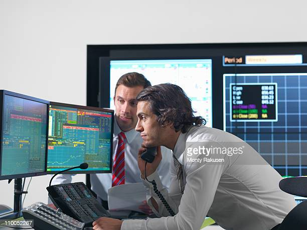 Financial traders with screens