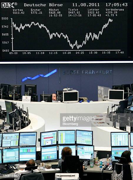 Financial traders work at their computers beneath a display of the DAX Index curve at the Frankfurt Stock Exchange in Frankfurt Germany on Thursday...