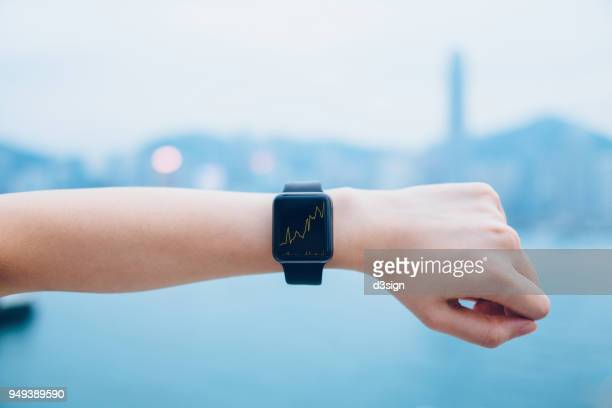 financial trading data shown on smart watch on human hand against urban city skyline - wrist stock pictures, royalty-free photos & images