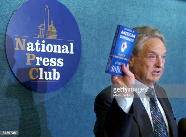 Financier and political activist, George Soros, holds up his new book as he briefs the press on his criticism of U.S. President George W. Bush's...