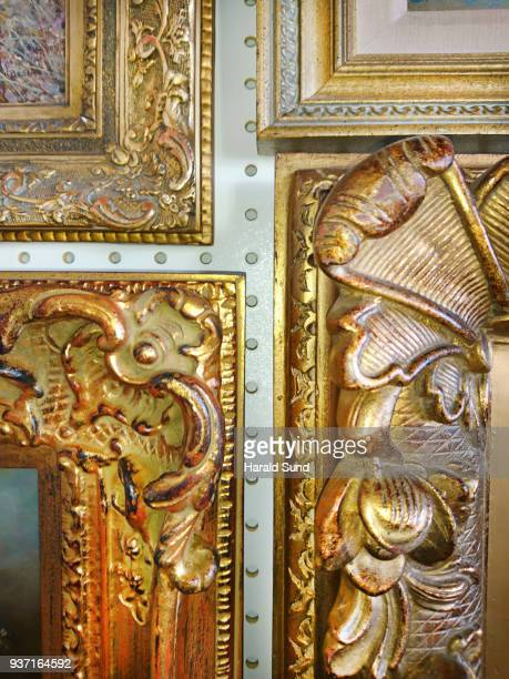 Fine art, ornate, gilded, carved, classic style picture frame detail close-up displaying oil paintings hung close together as a grouping on a wall.