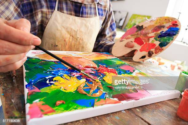 Fine art painter holding a palette and painting-close up