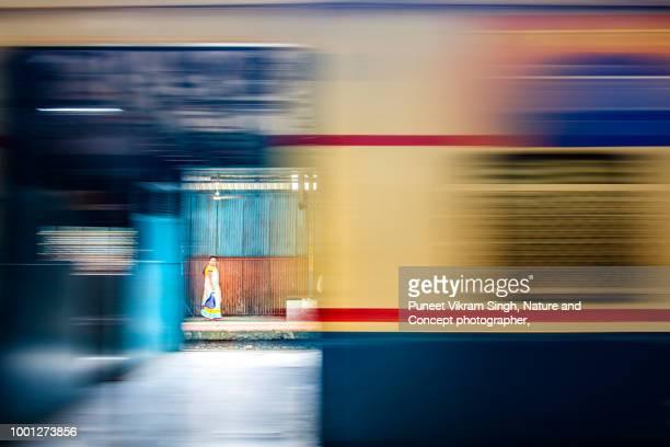 A fine art photograph of a woman walking on a railway platform