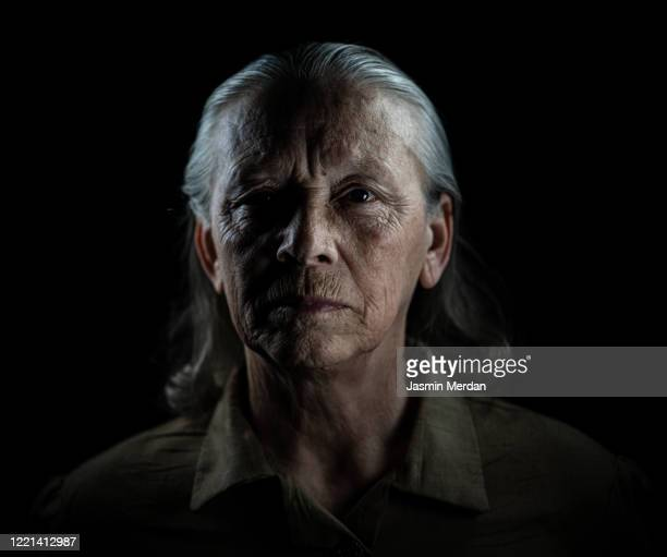 fine art portrait in dark of senior woman - high contrast stock pictures, royalty-free photos & images