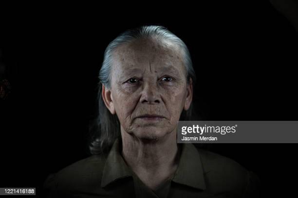 fine art portrait in dark of senior woman - parte del cuerpo humano fotografías e imágenes de stock