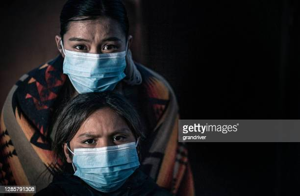 a fine art portrait of a fearful native american sister and her little brother, wearing protective masks from covid19 - indigenous culture stock pictures, royalty-free photos & images