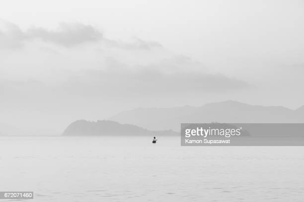 Fine art scene of fishing of fisherman in sea/ocean with collapse wooden pole in black and white