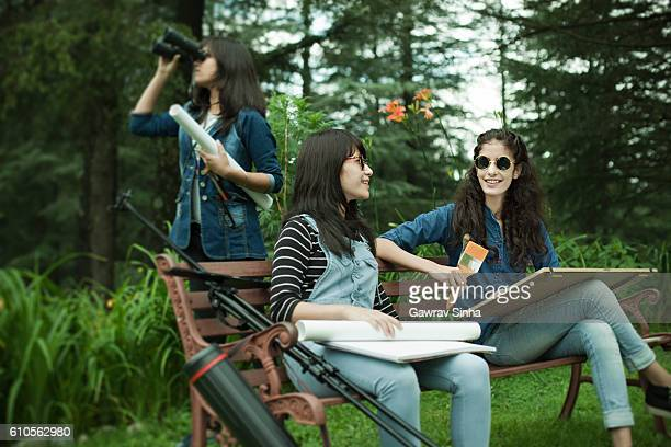 Fine Art students with drawing and painting equipments in park.