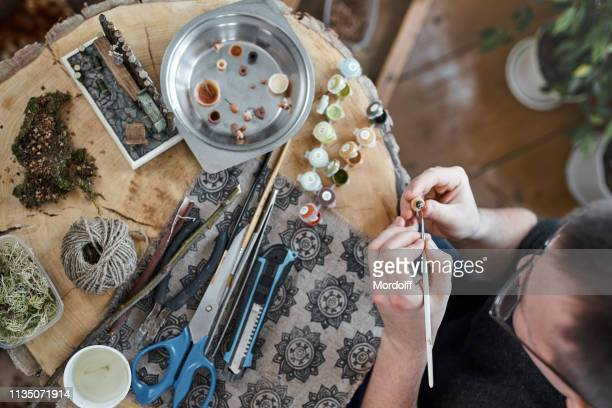 fine art. young master is coloring miniature flower in pot - drawing art product stock pictures, royalty-free photos & images