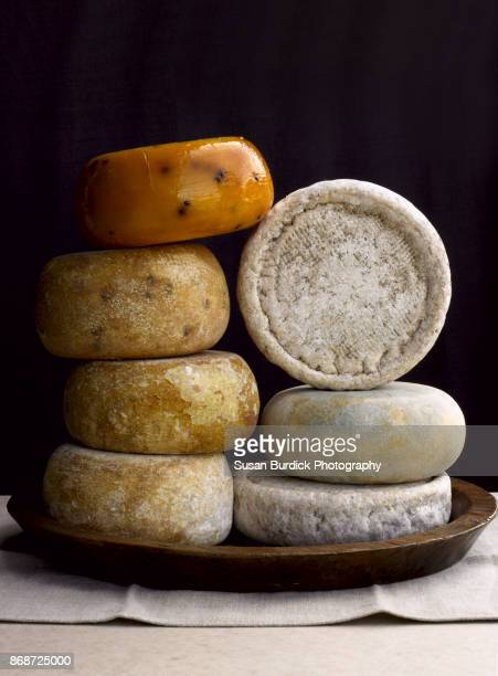 Fine artisan made sheep, cow and goat cheese wheels stacked in a still life composition