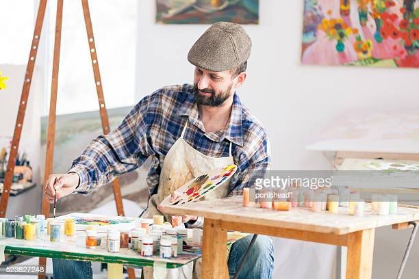 Fine artist painting at his workshop