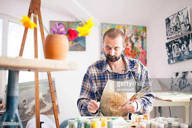 Fine artist painting at his workshop-looking at vase with flowers