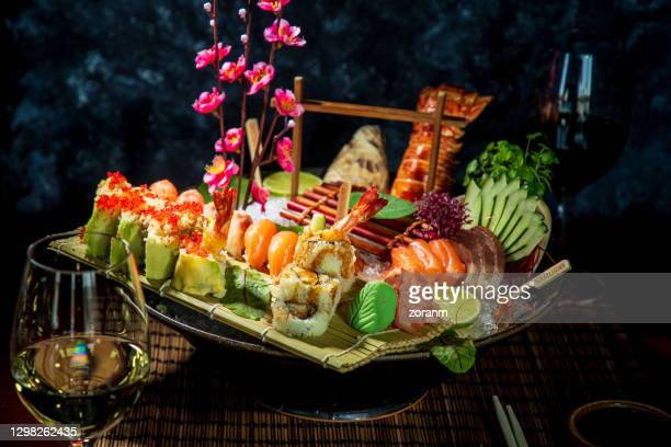 fine choice of sushi and sashimi served with wasabi paste and ginger on a decorated plate - wasabi paste stock pictures, royalty-free photos & images