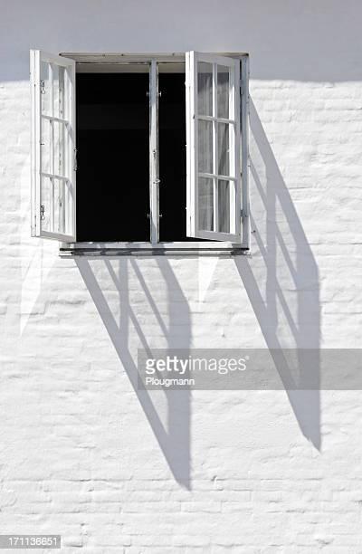 Fine vieille fenêtre sur mur blanc
