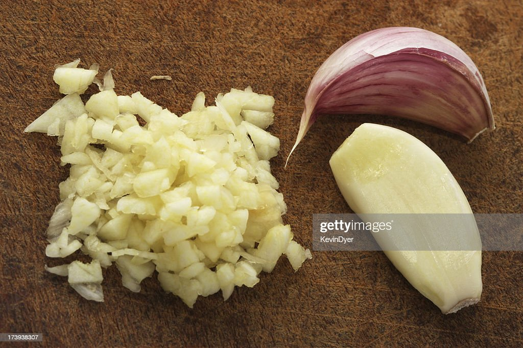 Finely chopped garlic on a wooden cutting board : Stock Photo