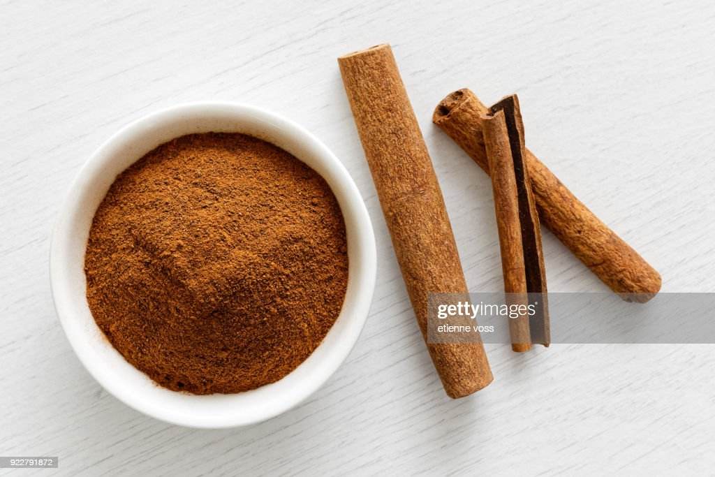 Finely ground cinnamon in white ceramic bowl isolated on white wood background from above. Cinnamon sticks. : Stock Photo