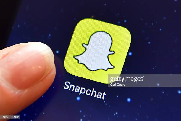 A finger is posed next to the Snapchat app logo on an iPad on August 3 2016 in London England