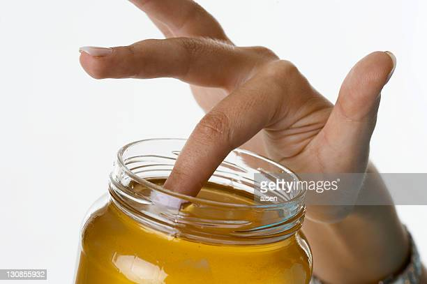 A finger is sticking in a glass full of honey