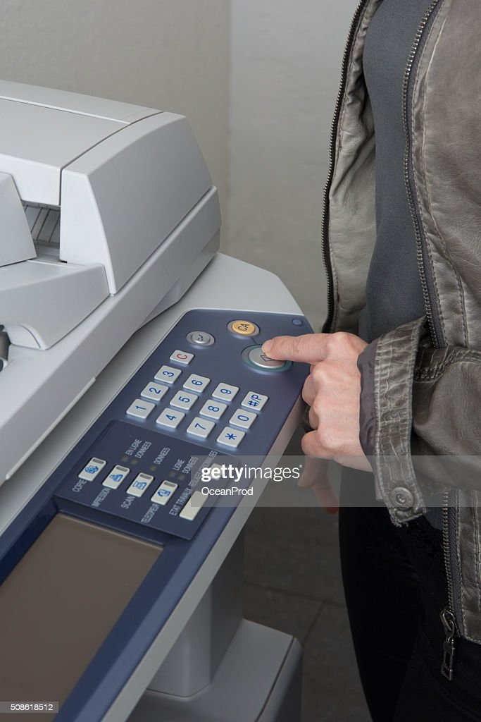 Finger of a woman is pressing the copymachine buttons : Stock Photo