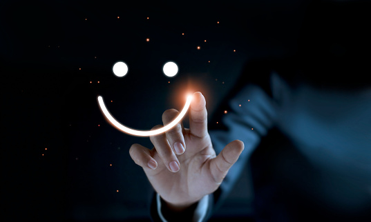 Finger of businessman touching and drawing face emoticon smile on dark background, service mind, service rating. Satisfaction and  customer service concept. 1127257331