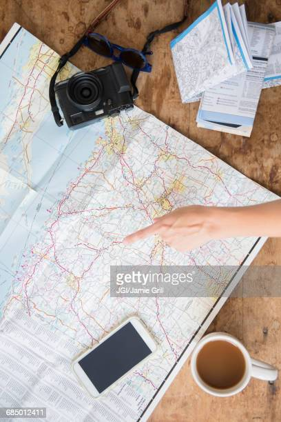 Finger of Caucasian woman pointing at map