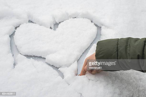Finger of little boy carving a heart in snow on a car