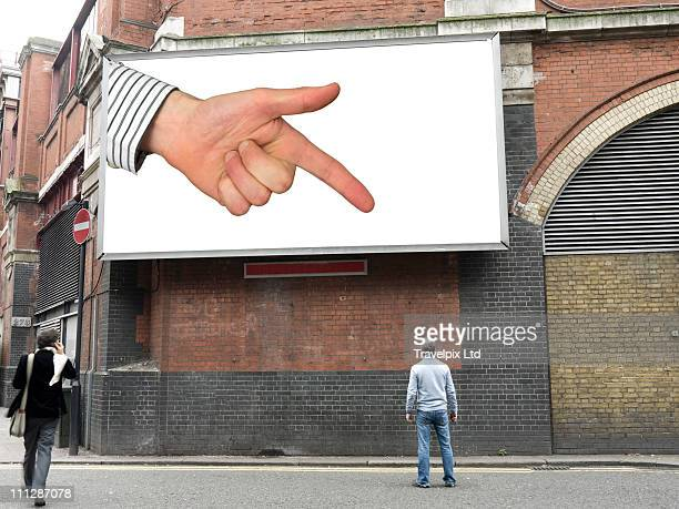 Finger on Billboard pointing at man