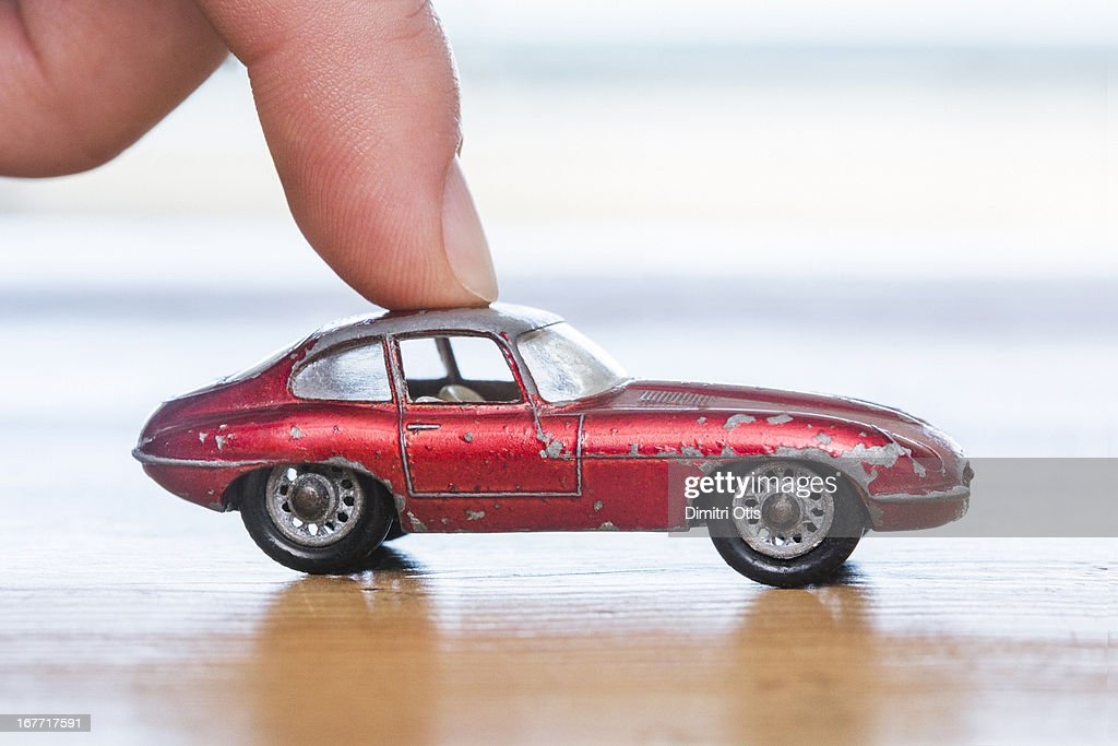 Finger placed on red aged toy car : Stock Photo