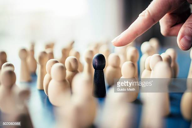 Finger pointing at a black pawn.