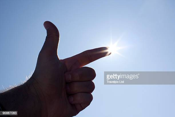 Finger pointing at the sun