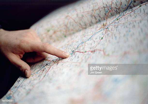 finger pointing on a map - karte navigationsinstrument stock-fotos und bilder