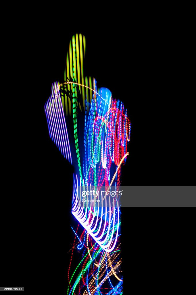Finger pointing up with light trails on black : Stock Photo