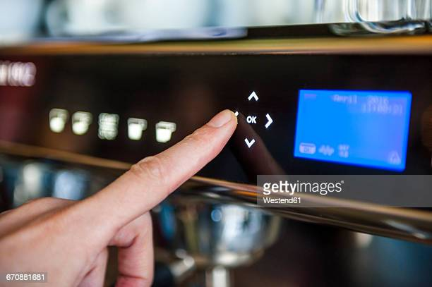 Finger pushing digital button on coffee machine