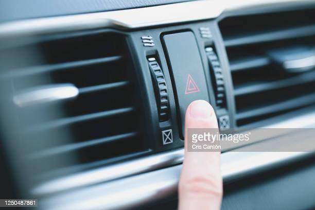 finger pushing warning light in car - sinal de emergência informação imagens e fotografias de stock