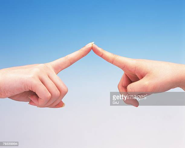 Finger tips of two women touching each other