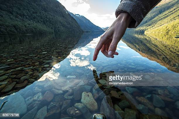 Finger touches surface of mountain lake, New Zealand