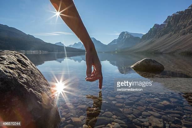 Finger touches surface of mountain lake, spectacular landscape