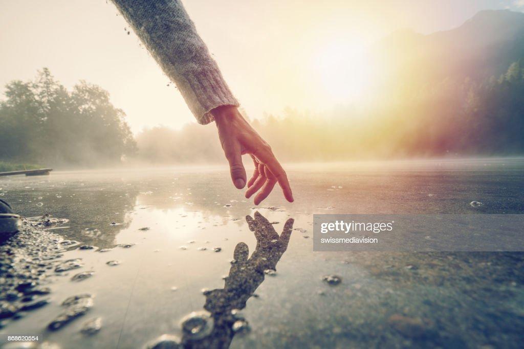 Finger berührt Oberfläche des Bergsees, Schweiz : Stock-Foto