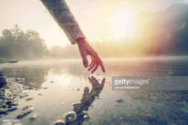 finger touches surface of mountain lake, switzerland - water stock pictures, royalty-free photos & images