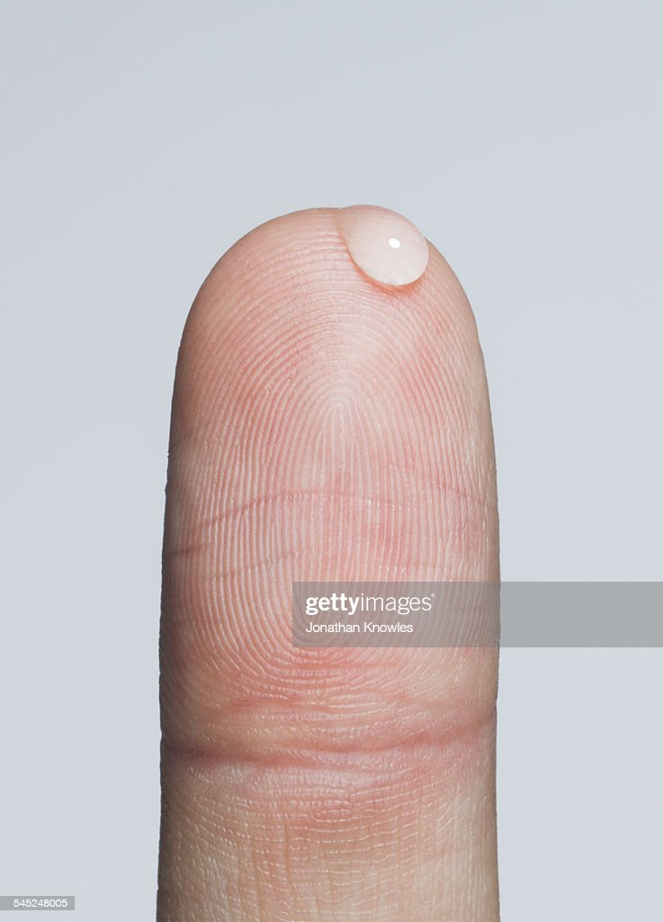 Finger with a bead of water : Stock Photo