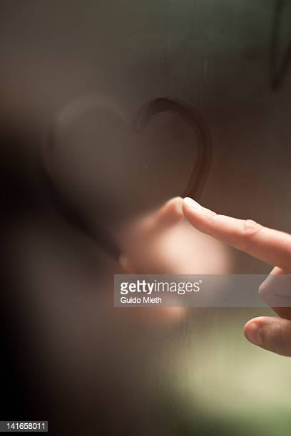 finger writing heart on steamy mirror - mirror steam stock photos and pictures