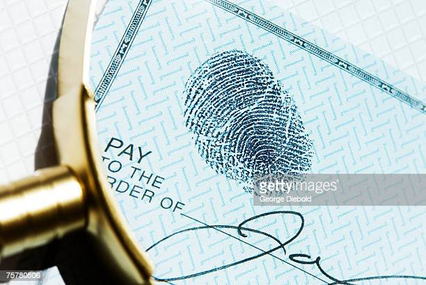 Fingerprint on cheque under magnifying glass