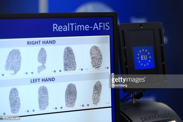 Fingerprints sit on a biometric data display screen beside a fingerprint scanner showing a European Union flag at the Dermalog Identification Systems...
