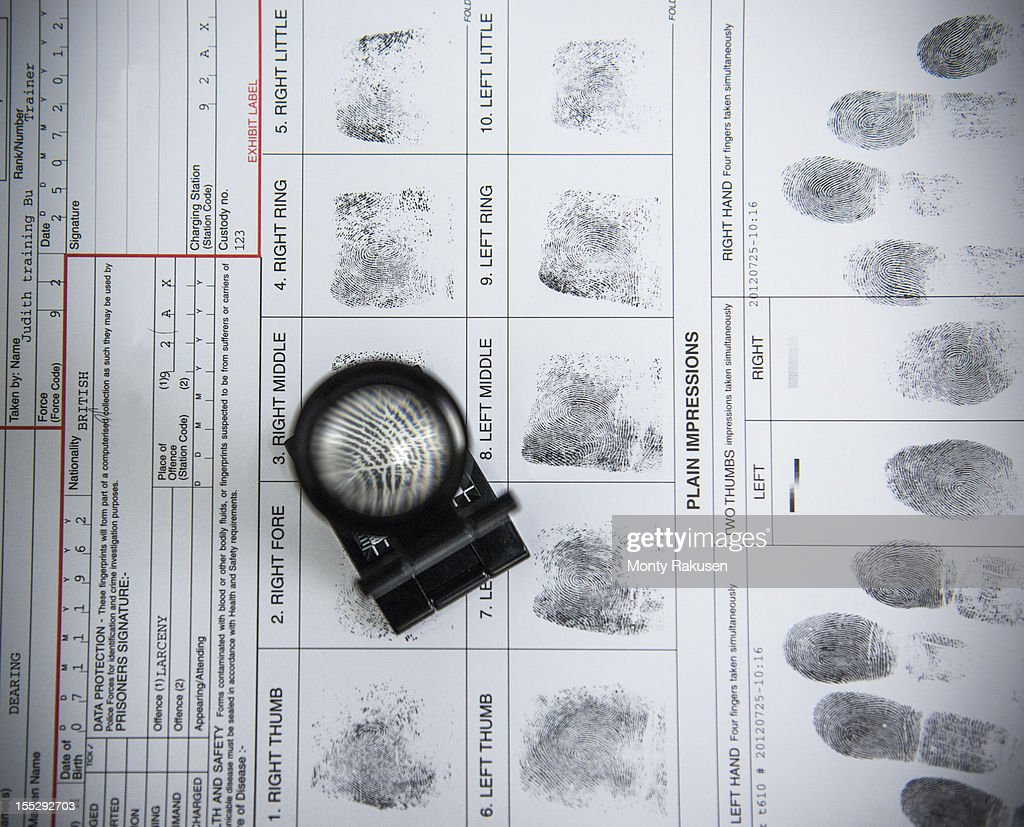Fingerprints with loupe on arrest form in forensic laboratory : Stock Photo